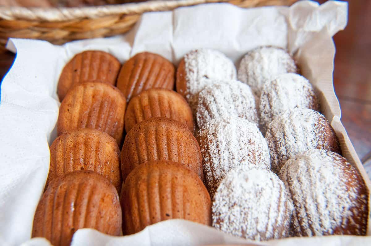 Magdalenki cynamonowo miodowe ułożone w pudełeczku jedna za drugą jedna część posypana cukrem pudrem