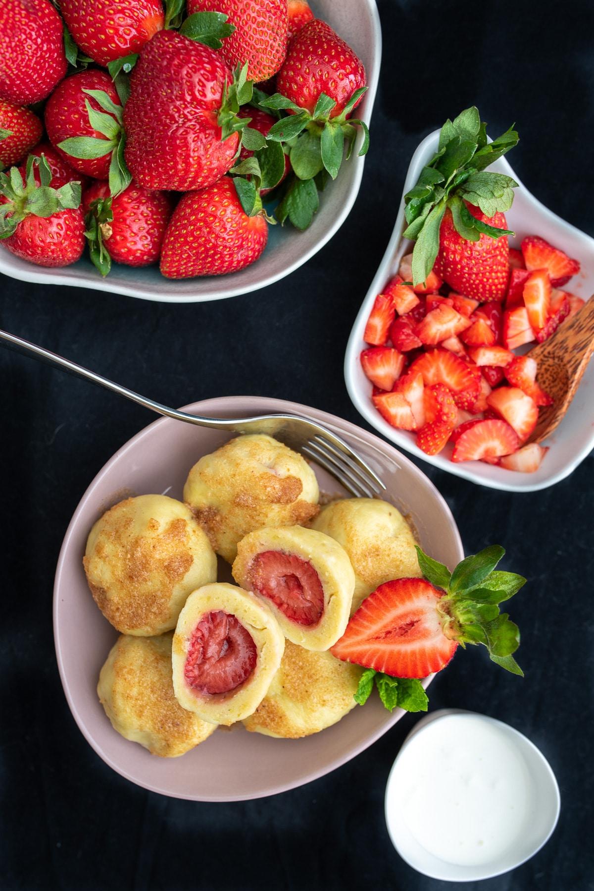 Knedle widziane z góry z nadzieniem ze świeżych truskawek, obok miseczki z truskawkami i śmietaną