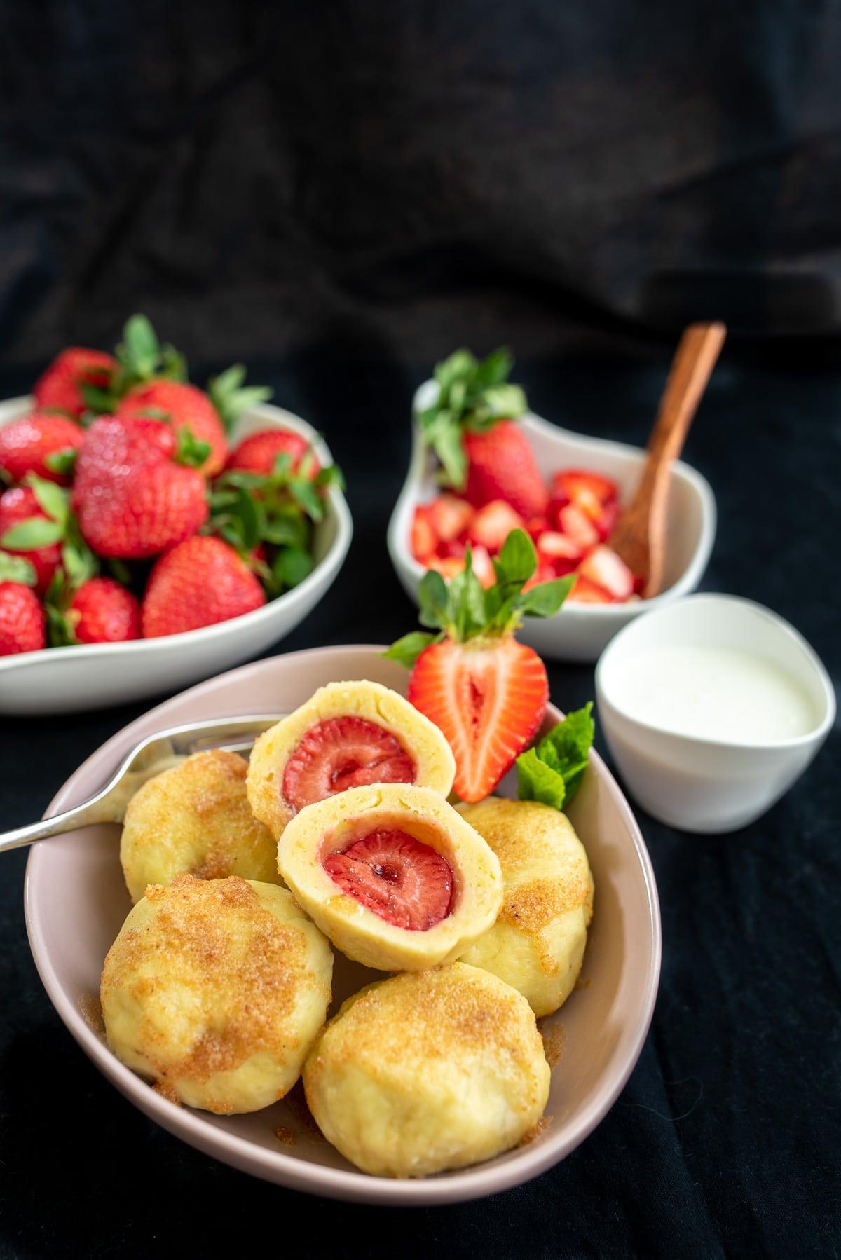knedle na różowym talerzu polane masłem z tartą bułką, w tle miseczka z truskawkami i śmietaną