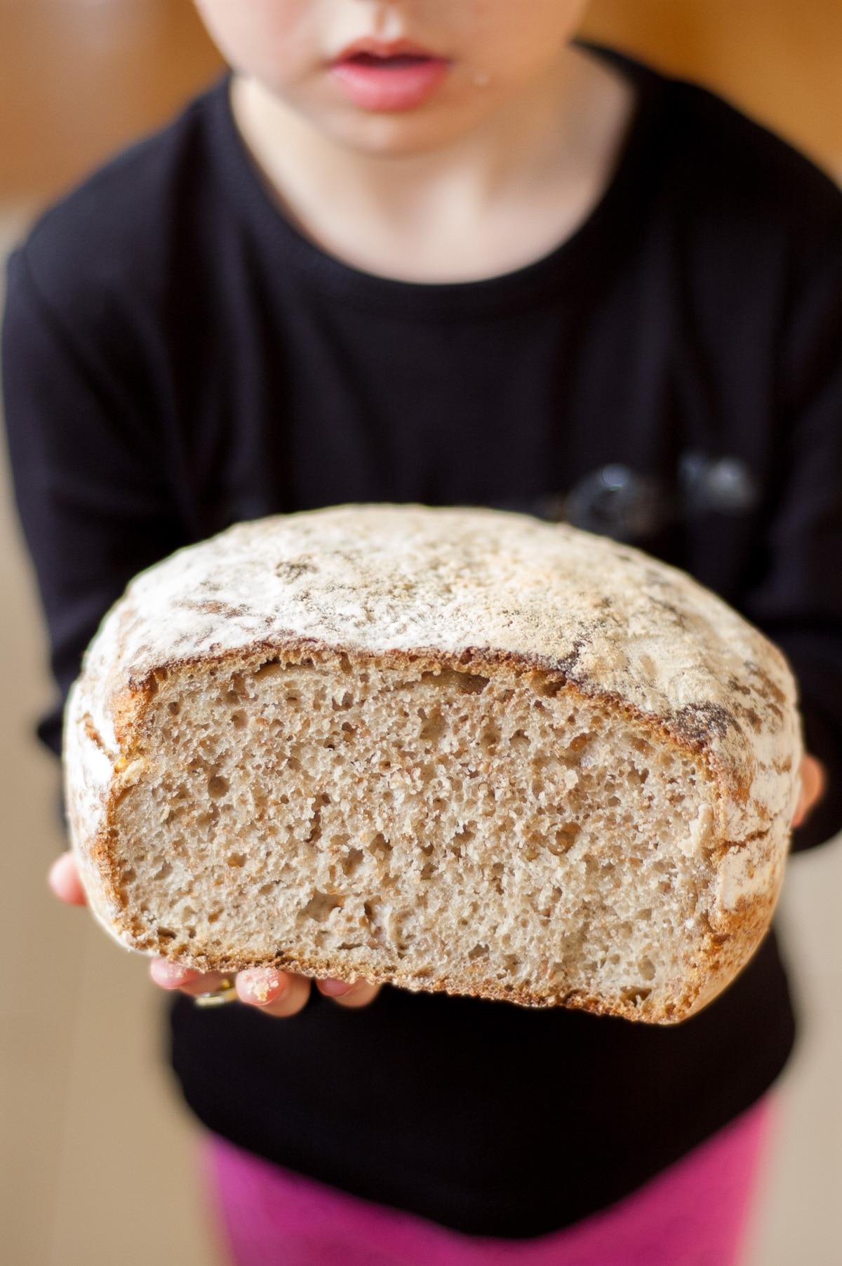 dziecko trzyma chleb w rączkach, widać wnętrze chleba