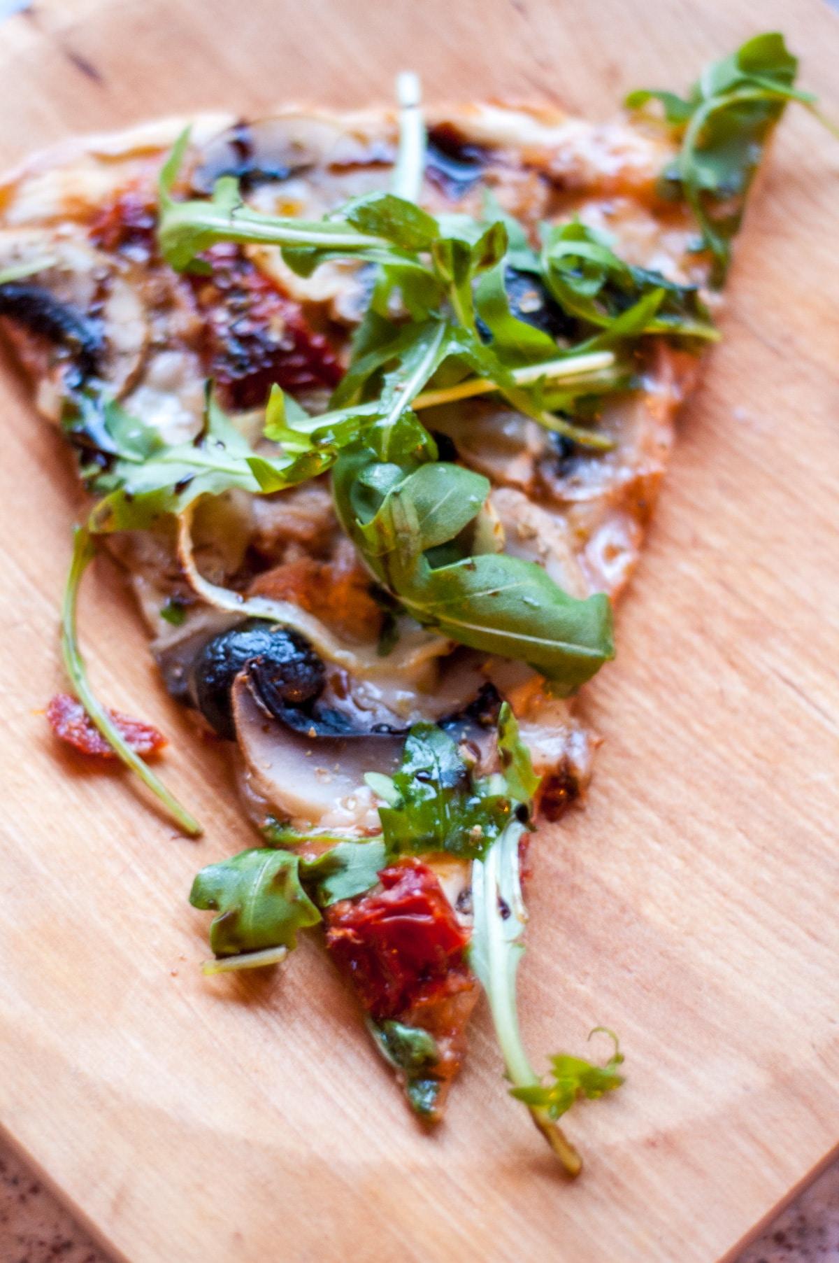trójkąt pizzy z rukolą, tuńczykiem i czarnymi oliwkami