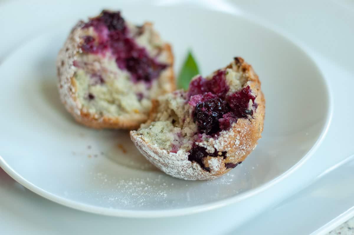Muffinki z jeżynami na talerzu rozerwane na pół