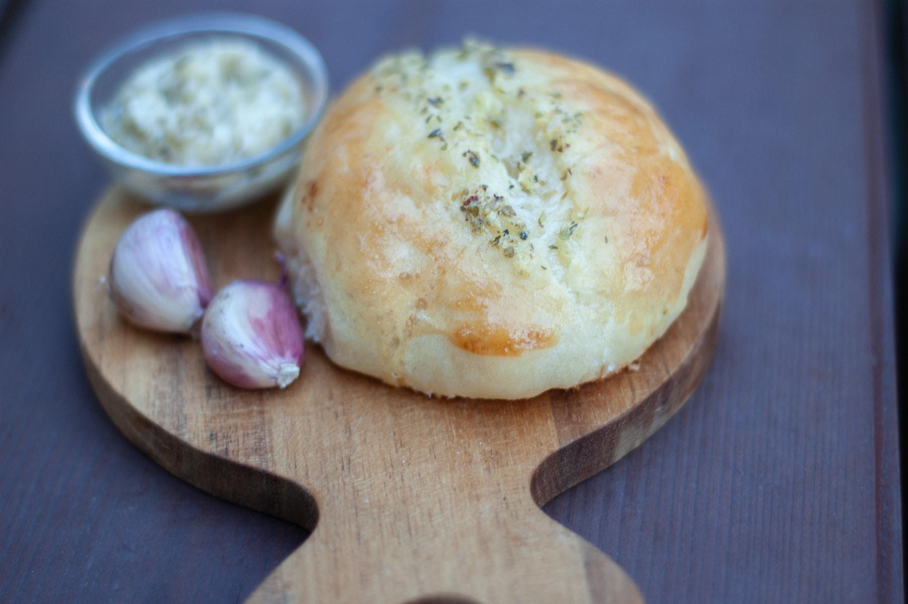 bułeczka na desce obok czosnek i masło
