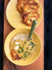 krem z kurek w żółtym talerzy obok placki ziemniaczane