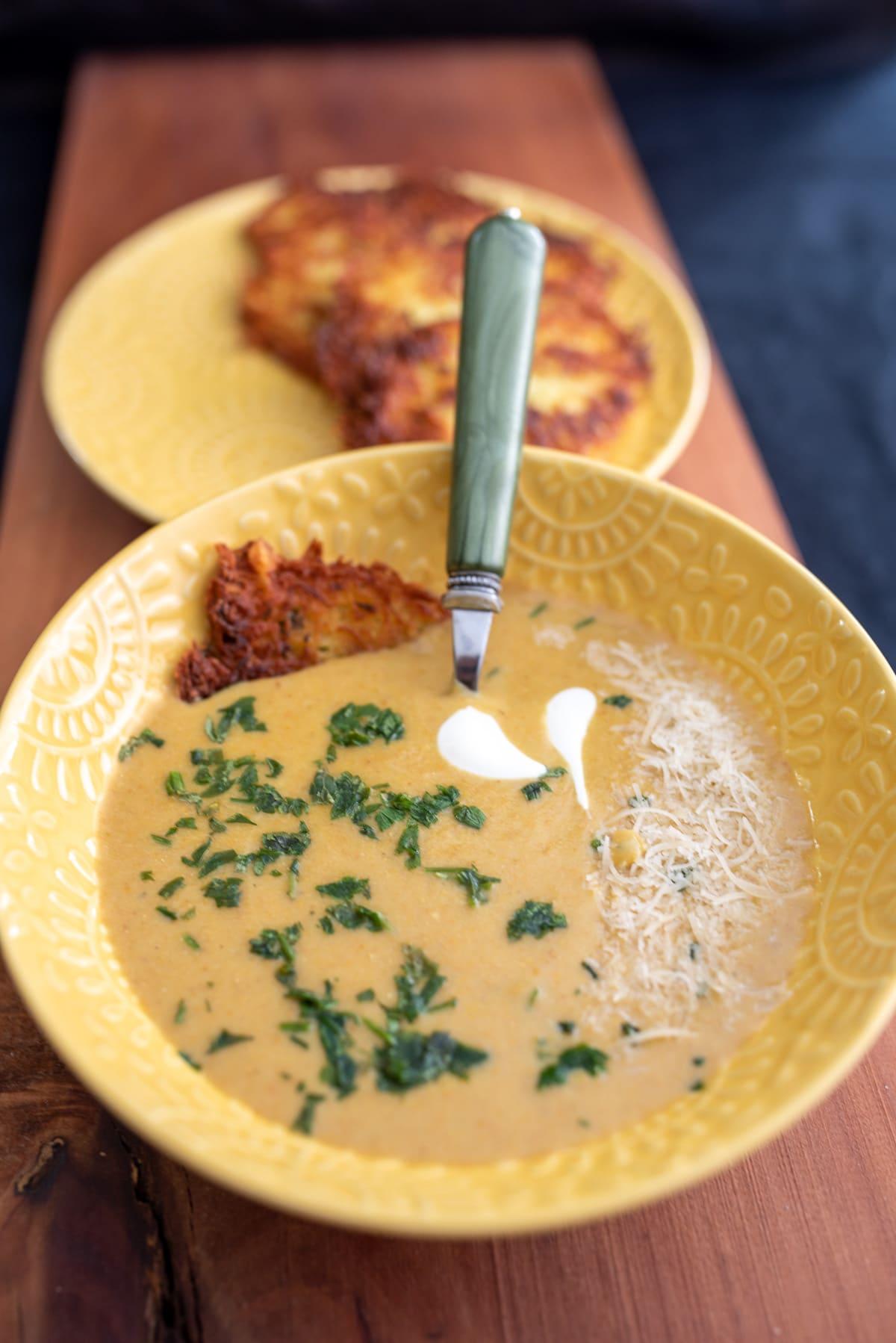 zupa w żółtej misce udekorowana pietruszka podana z plackami ziemniaczanymi
