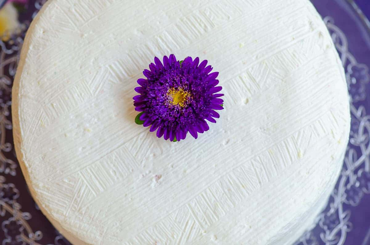 widok z góry na tort ozdobiony białym kremem, po środku fioletowy kwiat
