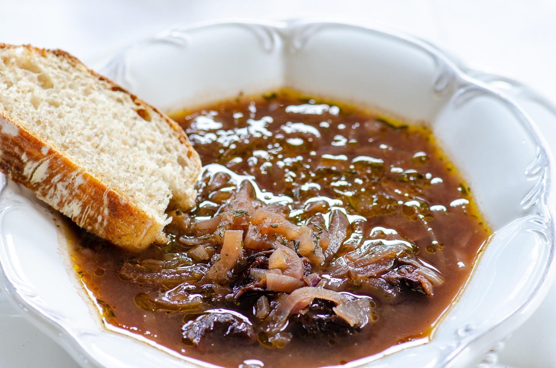 Talerz zupy z czerwonej cebuli i suszonych śliwek z kromką chleba