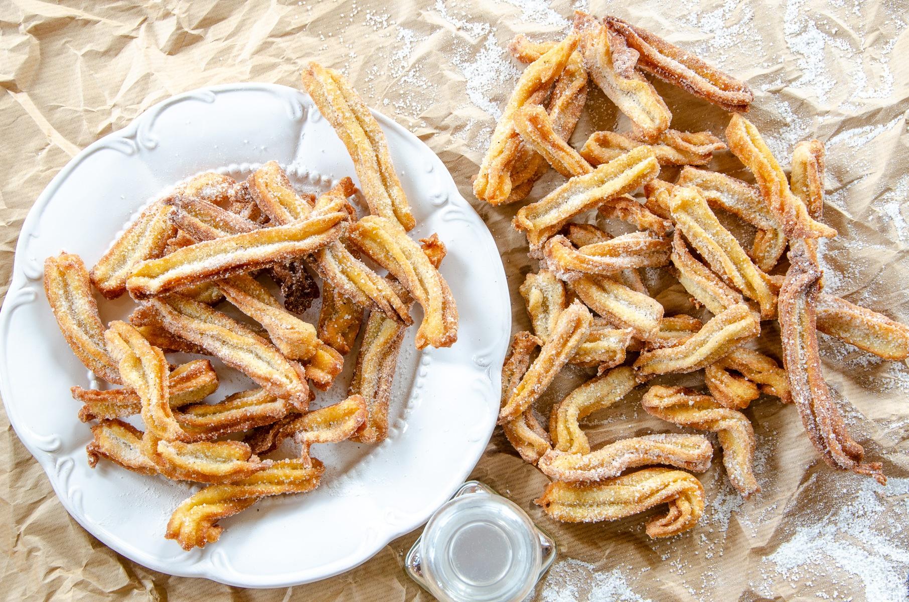 churros z przyprawą piernikową podane na talerzu obtoczone w cukrze z przyprawami