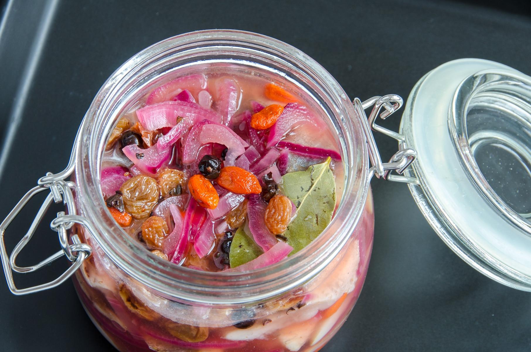 śledź z czerwoną cebulą w słoiku z rodzynkami i jagodami goji