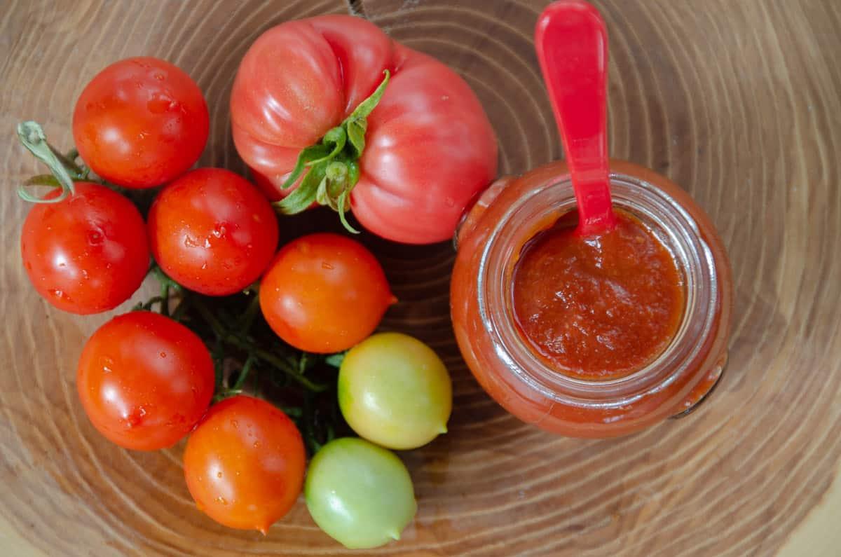 ketchup domowy w słoiczku obok świeże pomidory.
