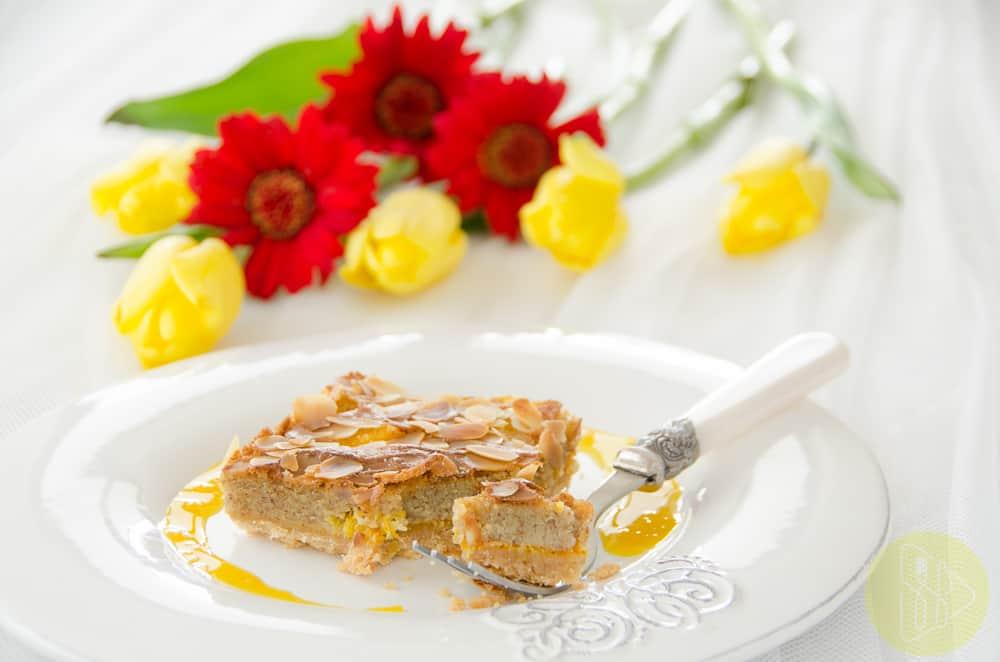 Tarta migdałowo pomarańczowa na białym talerzu w tle kwiaty.