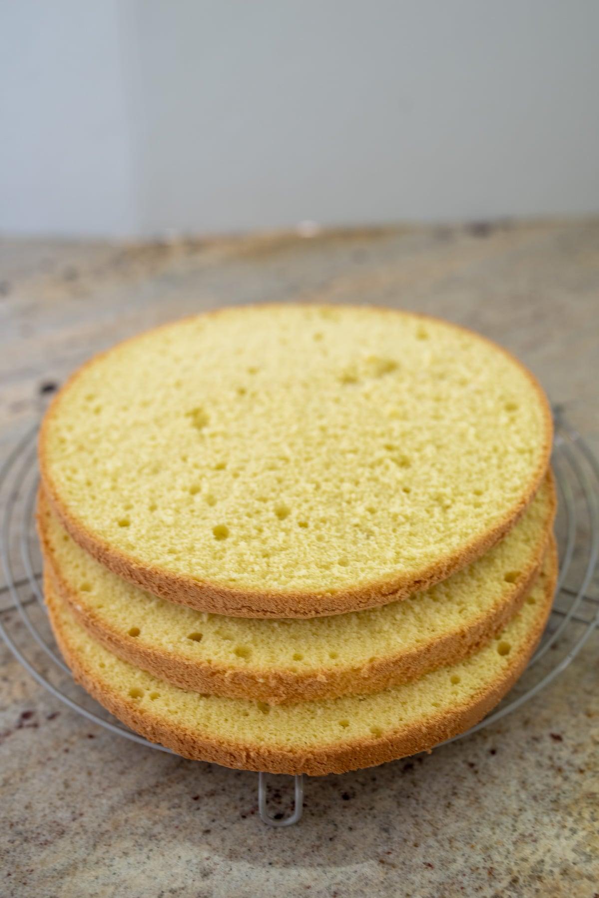 trzy żółciutkie blaty biszkoptu ułożone na kratce do studzenia ciast