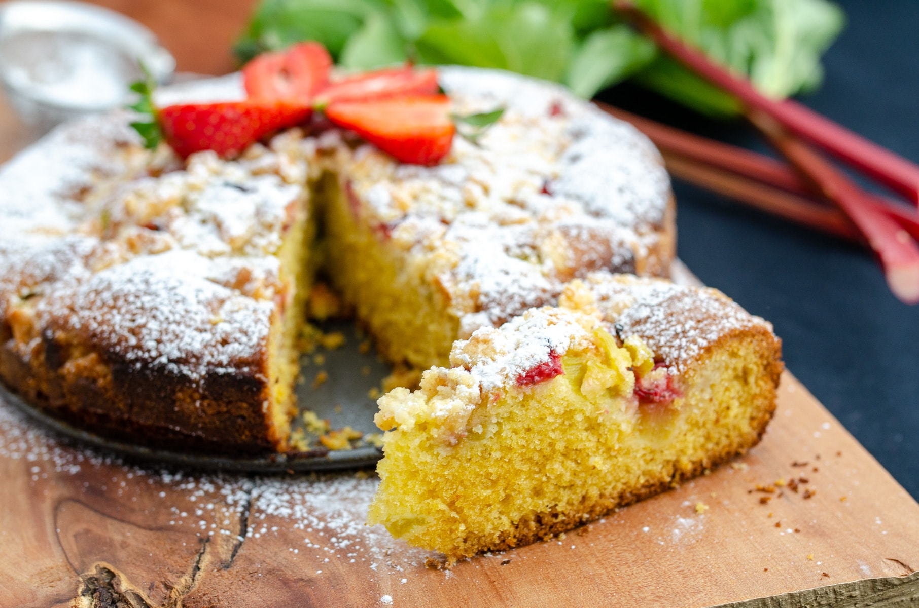 puszysty kawałek ciasta z rabarbarem na drewnianej desce w tle całe ciasto