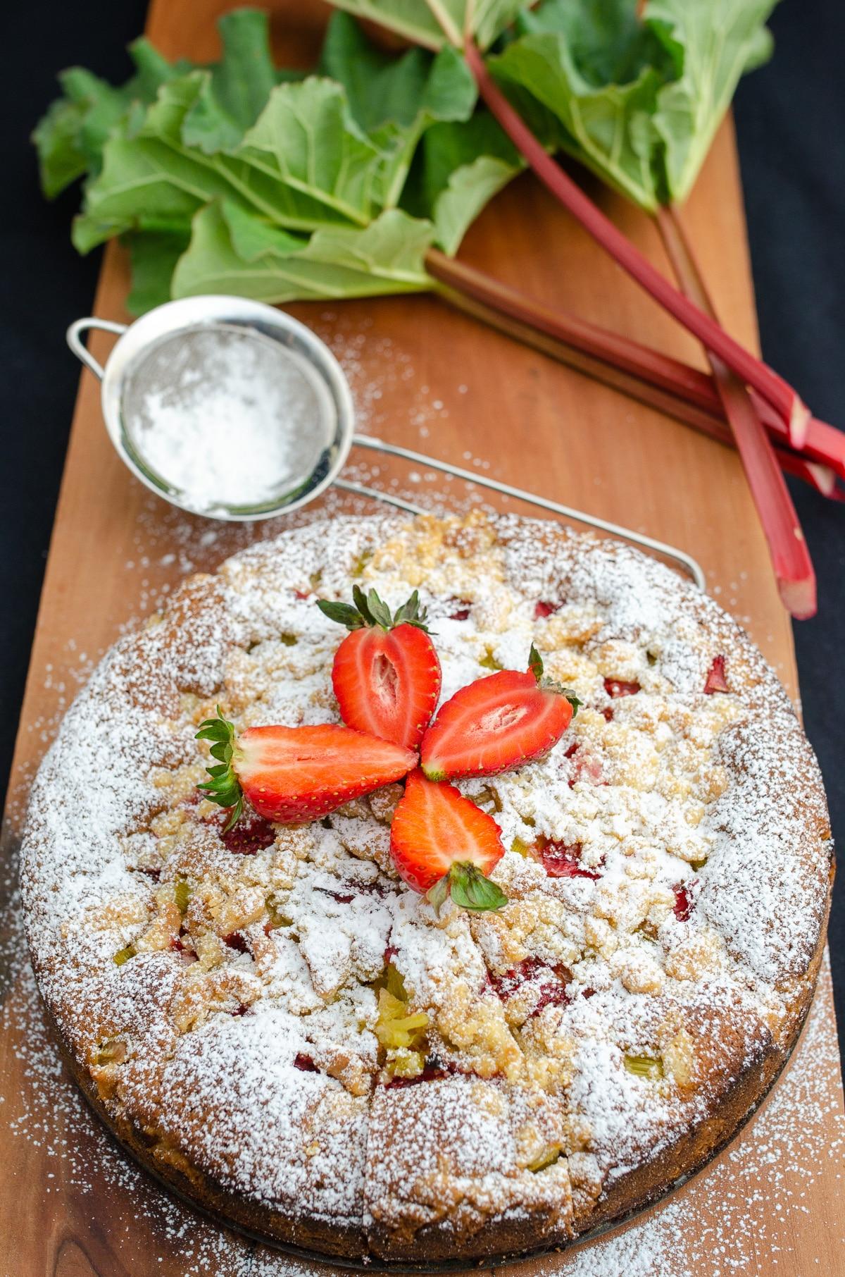Ciasto posypane cukrem pudrem udekorowane truskawkami w tle rabarbar z listkami