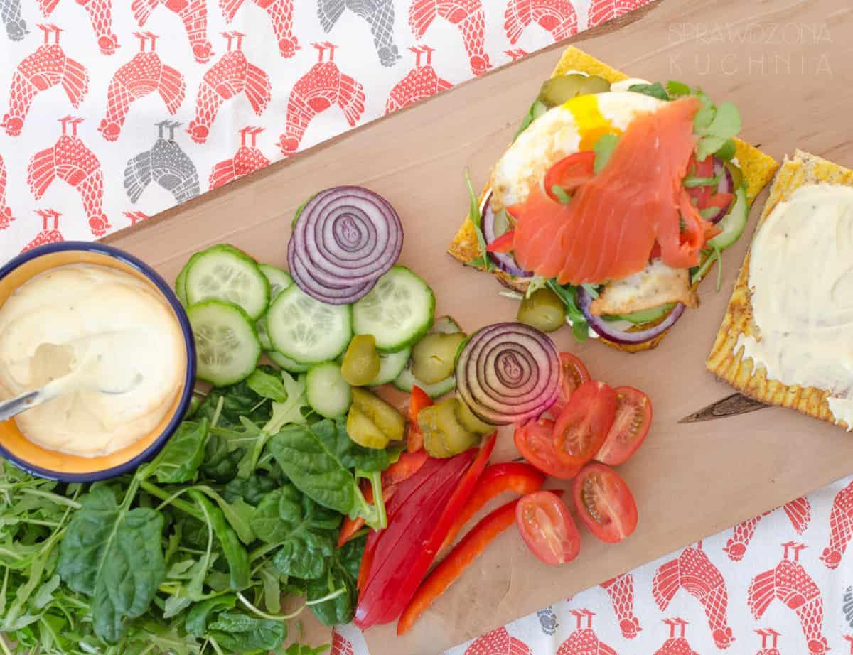 Chleb warzywny na którym przygotowano kolorową kanapkę z mnóstwem warzyw i sosem.