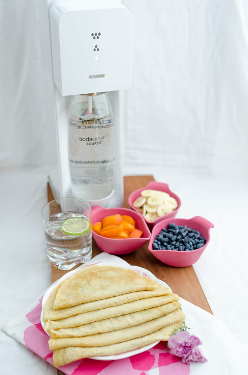 Naleśniki na wodzie gazowanej ułożone na talerzu w tle owoce w różowych miseczkach i biały syfon do wody.