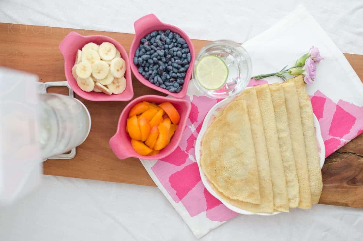 Naleśniki na talerzu na różowej ściereczce, obok owoce w różowych miseczkac.