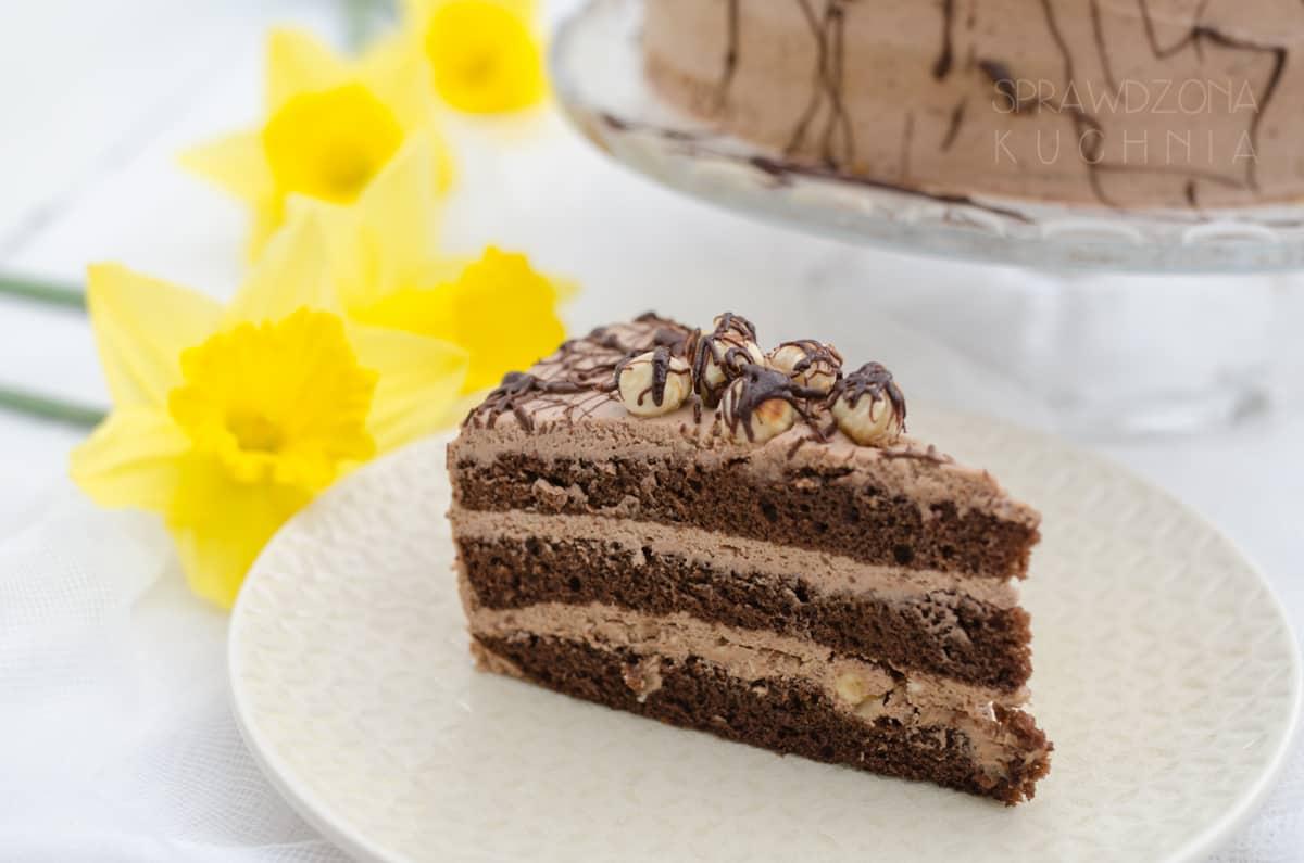 Kawałek tortu na talerzu w tle żonkile.