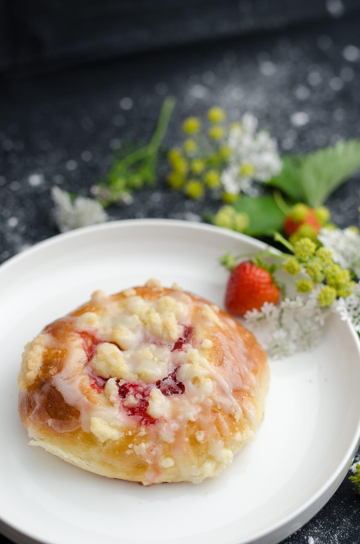 Drożdżówki z truskawkami i mang z kruszonką i dużą ilością lukru. Bułka na białym talerzu udekorowana truskawka i kwiatami.