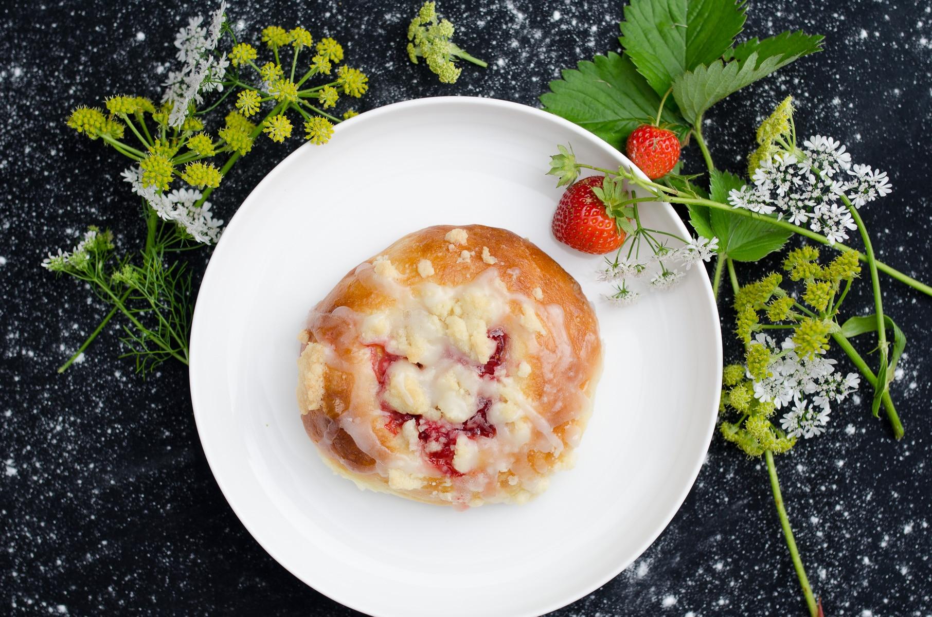 Rumiana drożdżówka z truskawkami, kruszonką i lukrem na białym talerzu ułożona na czarnym obrusie udekorowanym kwiatami polnymi i truskawkami.