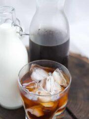 Kawa na zimno szklance z lodem w tle kawa w butelce i mleko.