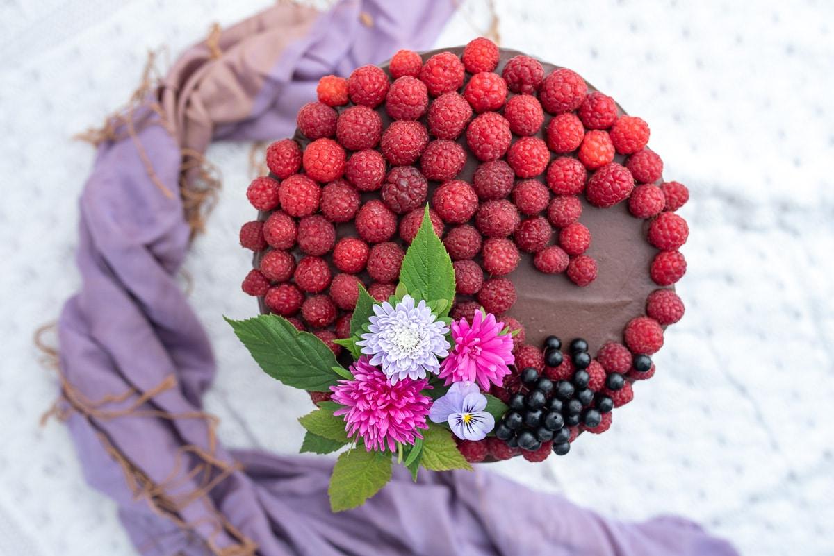 tort-czekoladowo-malinowy widok z góry, polany czekoladą i udekorowany świeżymi malinami oraz kwiatami