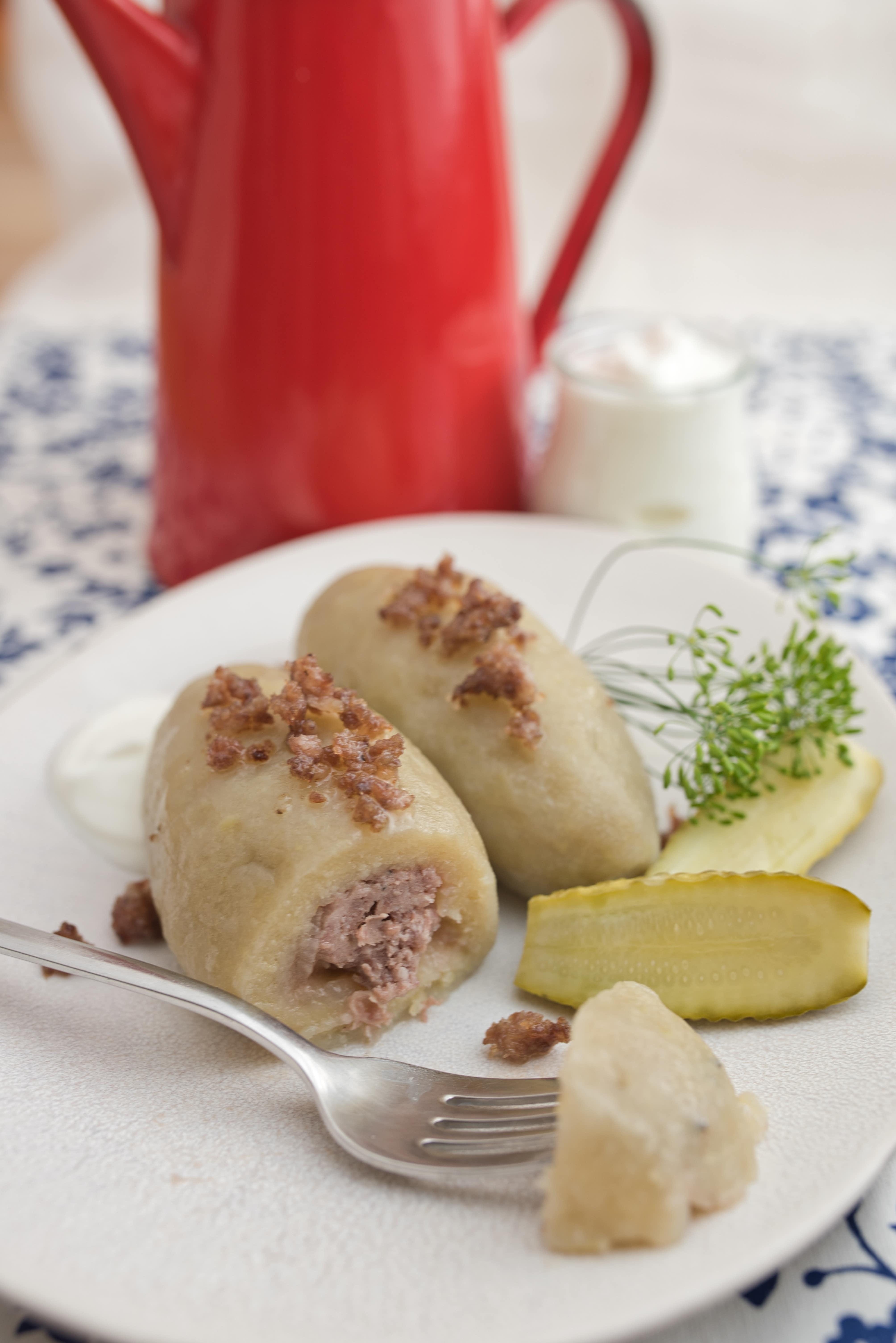 kartacze na talerzu okraszone cebulka i boczkiem, podane z ogórkiem kiszonym