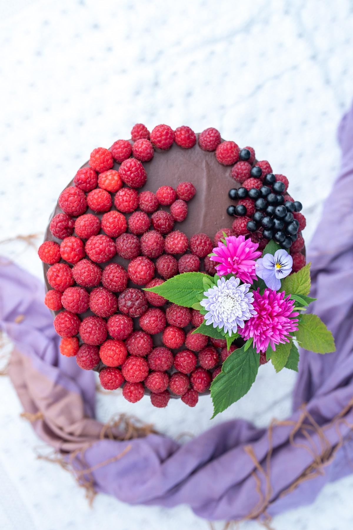 Widok z góry na tort polany polewą czekoladową i udekorowany malinami oraz świeżymi kwiatami
