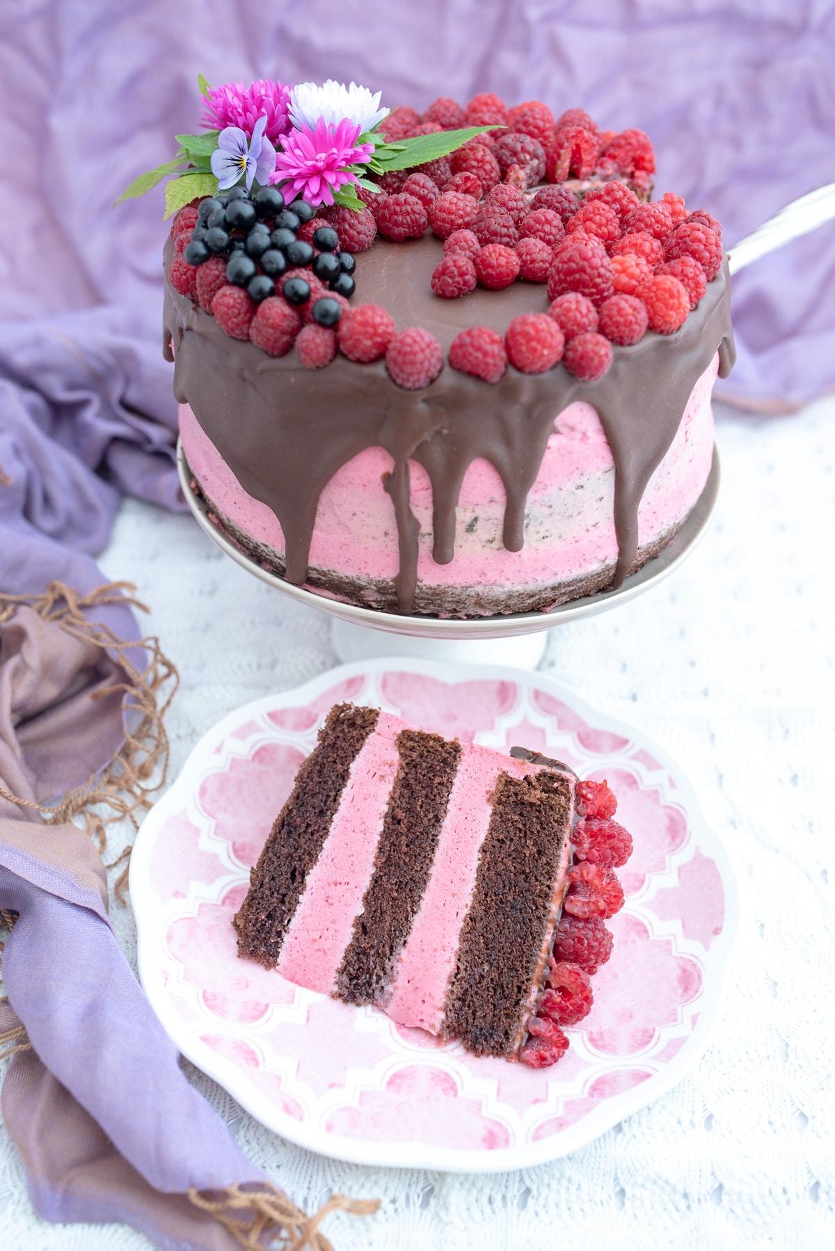 Kawałek tortu z czekoladowym biszkoptem przełożony musem malinowym
