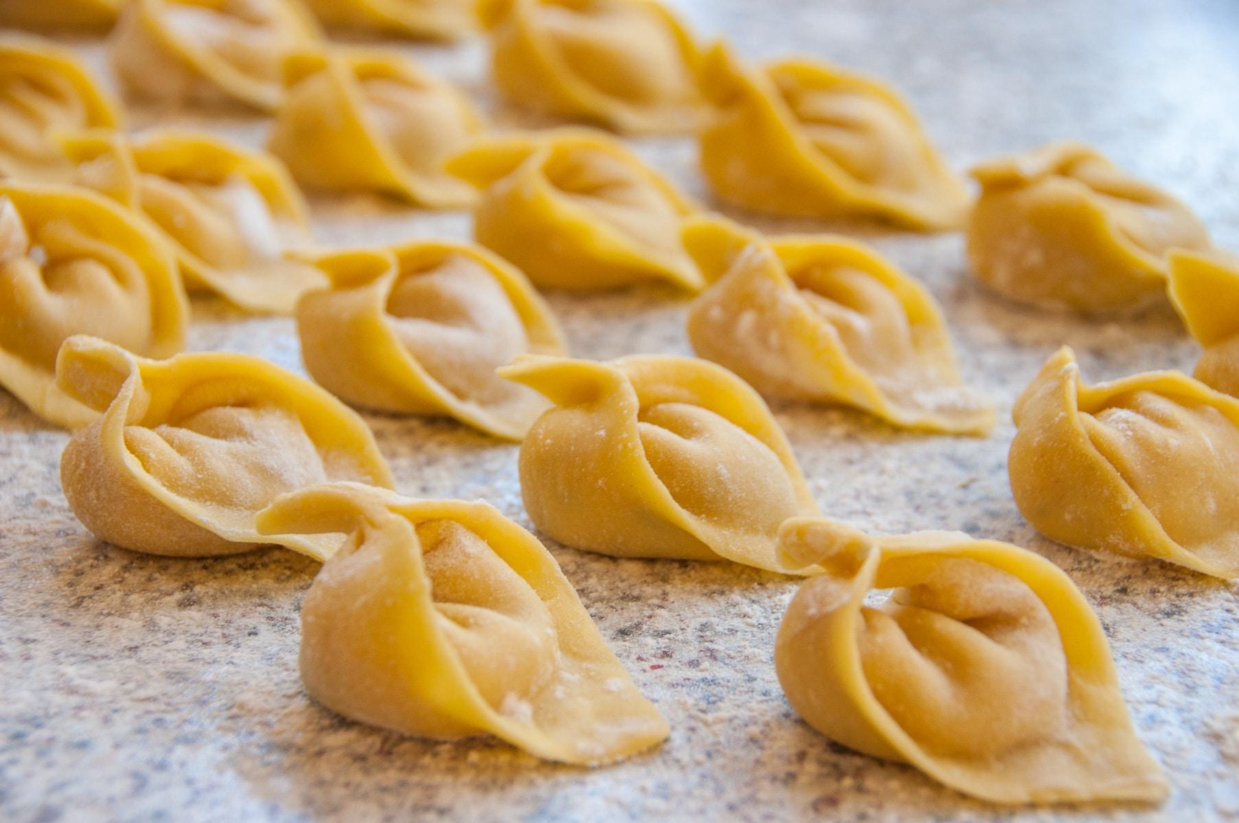 Surowe tortellini ułożone jeden obok drugiego na blacie posypanym mąką.