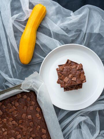 brownie na białym talerzu ułożone jedno na drugim obok żółta cukinia i ciasto w blaszce