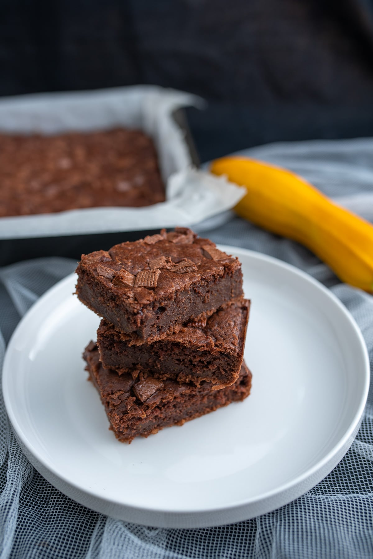 Apetyczne kwadraty brownie z kawałkami czekolady na wierzchu na białym talerzu w tle żółta cukinia