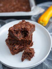 kawałek brownie na białym talerzu w tle cała blacha ciasta i żółta cukinia