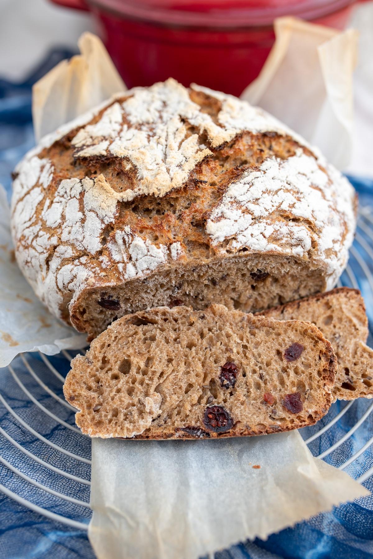 Rumiany chleb ułożony na kratce do studzenia, obok kromka chleba z żurawiną w miękiszu.