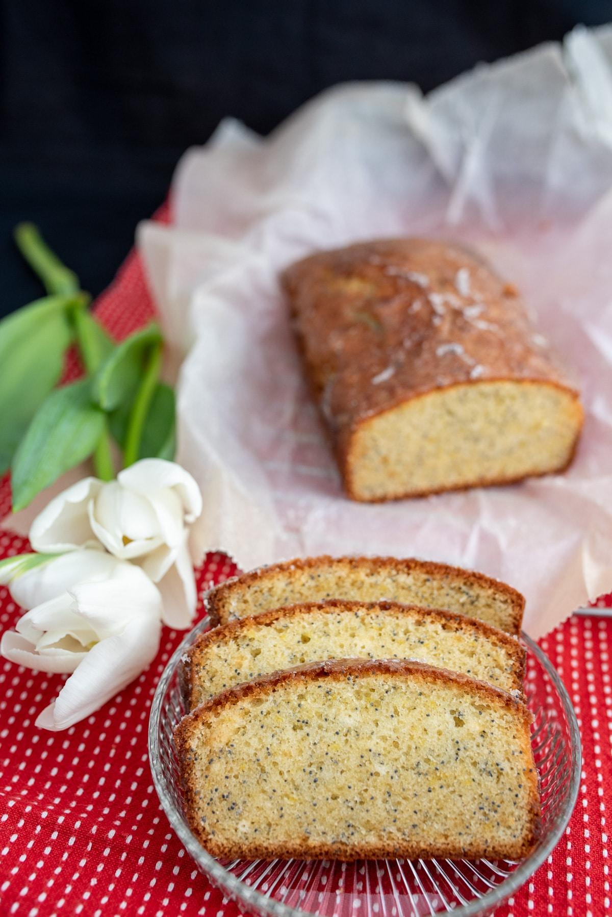 Trzy kawałki ciasta na szklanym talerzyku w tle pozostałe ciasto, po lewej stronie leżą białe tulipany