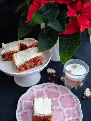 Kawałek ciasta na różowym talerzu w tle ciasto na paterze i czerwona gwiazdka betlejemska