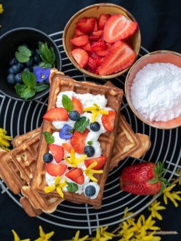 gofry z bitą śmietaną i owocami w tle miseczki z owocami