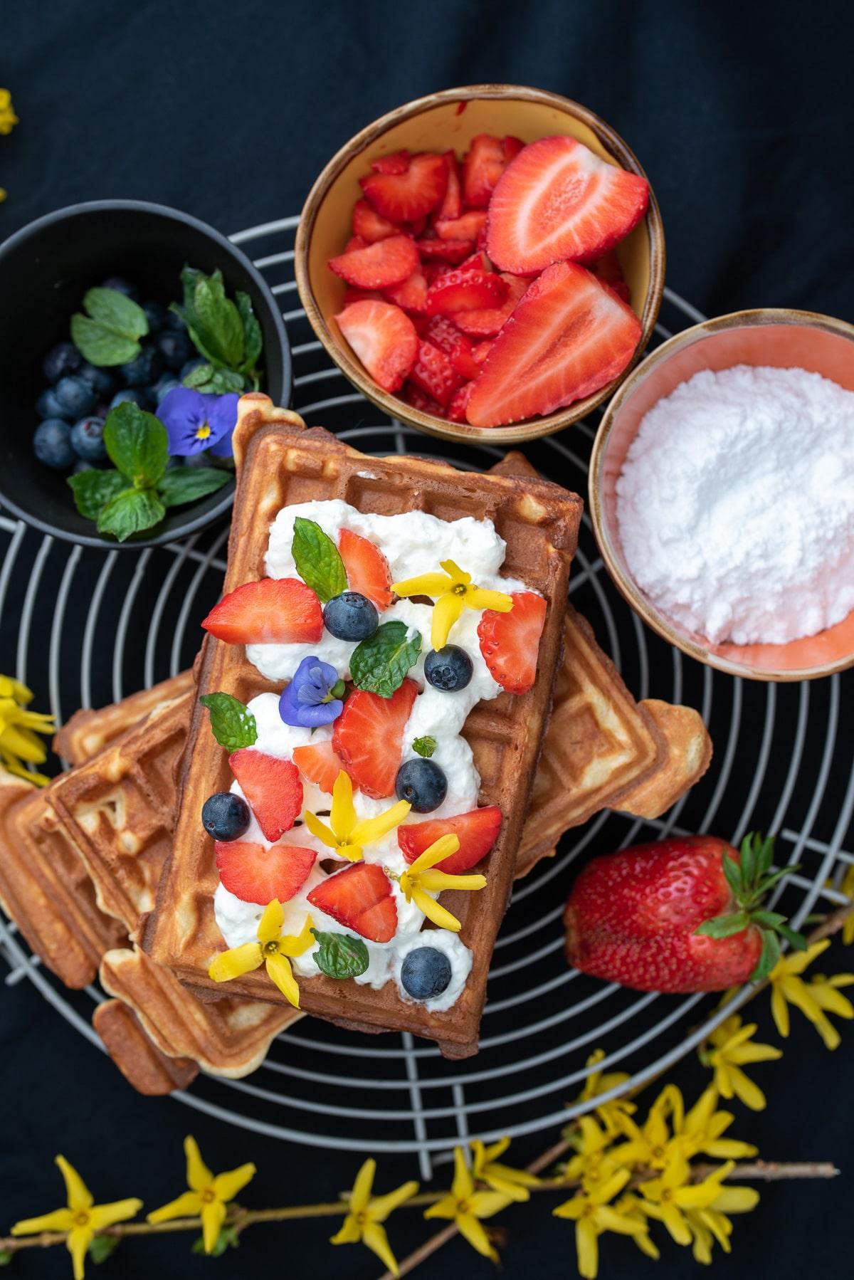 gofry z bitÄ… Å›mietanÄ… i owocami w tle miseczki z owocami