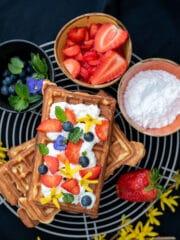 gofry na szarej kratce z owocami i bitÄ… Å›mietanÄ… obok kolorowe miseczki z owocami cukrem pudrem
