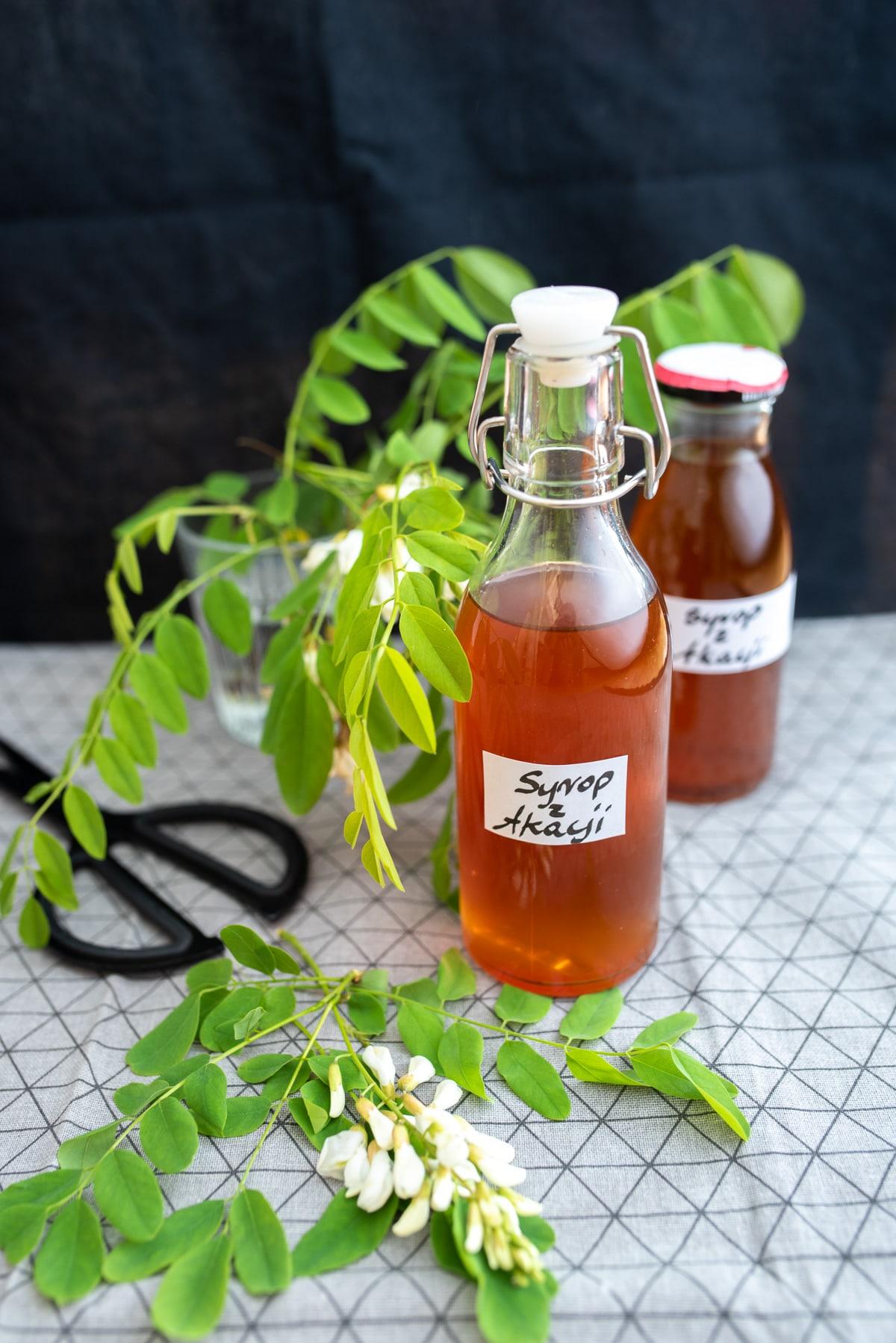 syrop z kwiatów akacji w butelkach na szarym obrusie ozdobionym kwiatami robinii