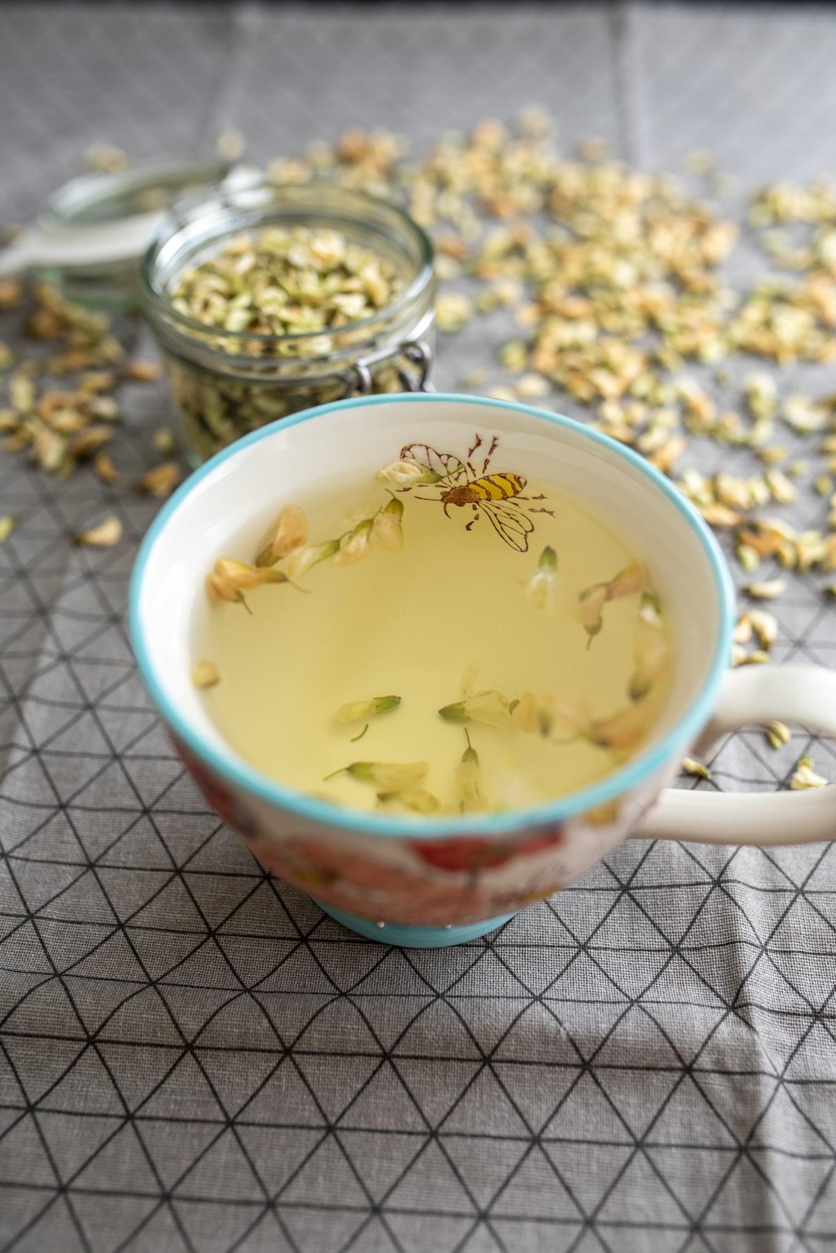 Herbata z akacji w kubku na szarym obrusie w tle słoiczek z suszem