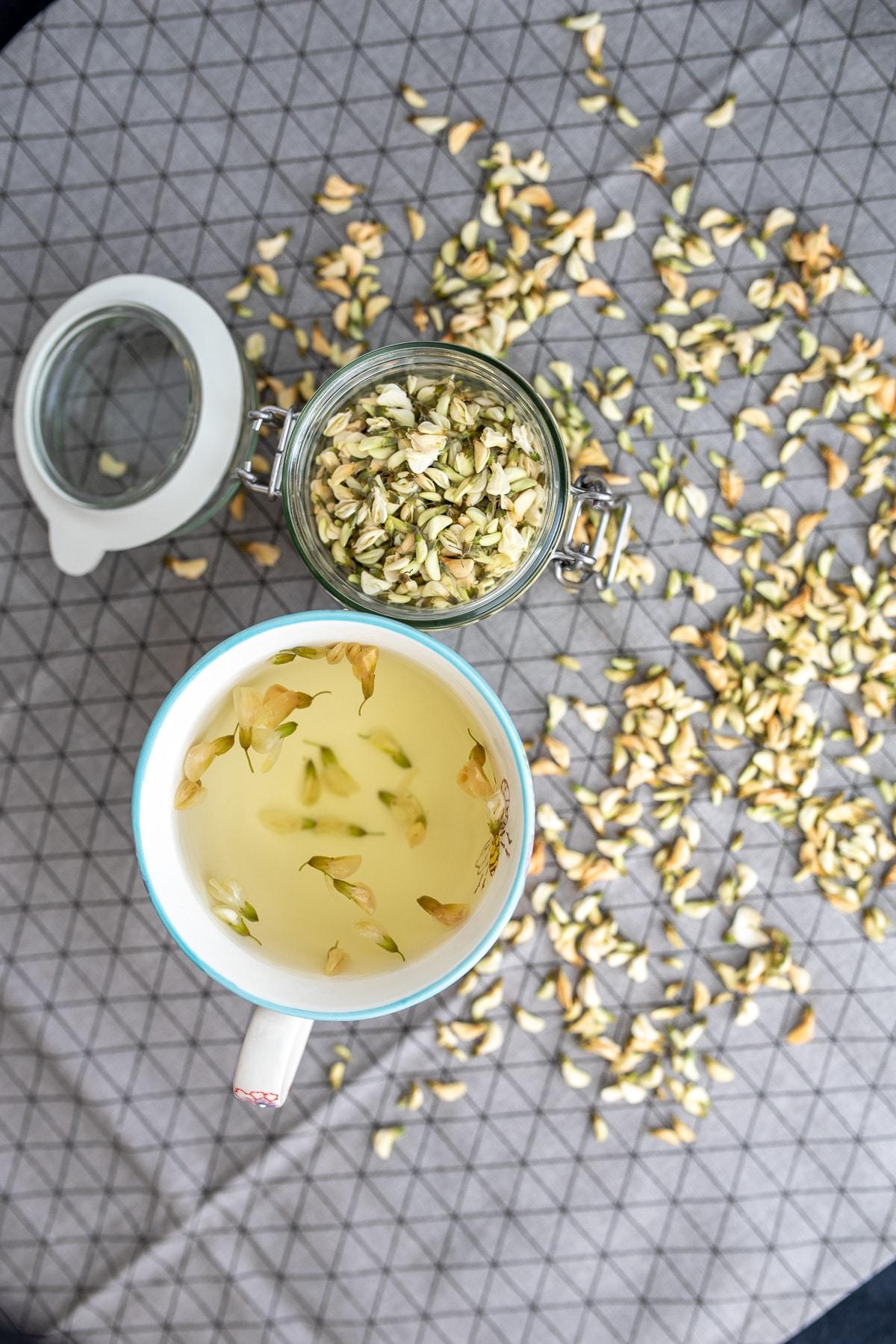 herbata zaparzona w kubku w tle rozsypana suszone kwiaty akacji