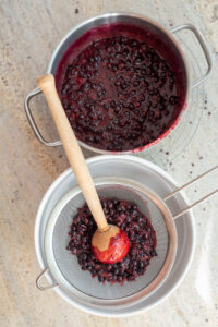 czarne porzeczki przecierane na sicie, obok garnek z owocami do przetarcia