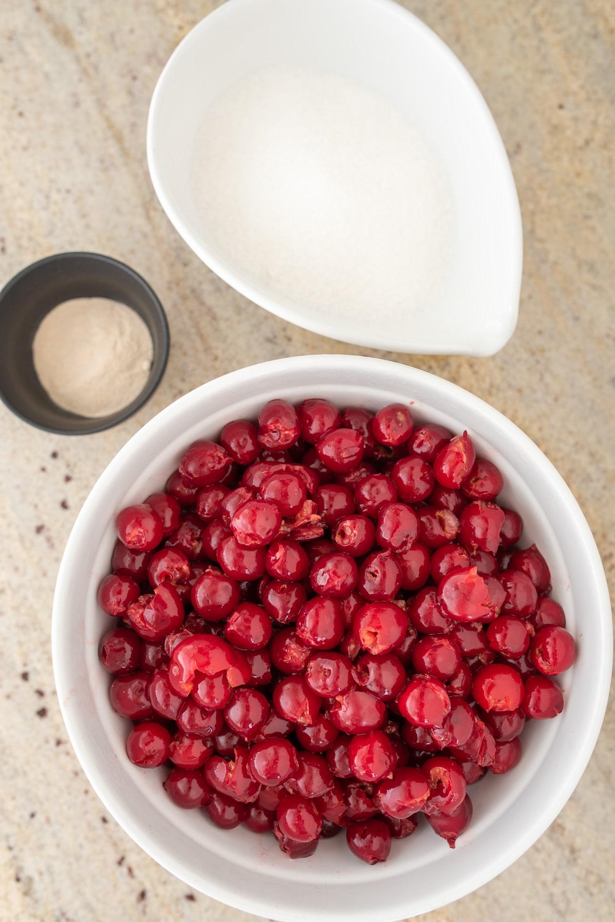 wydrylowane wiśnie w białej misce obok cukier i pektyna