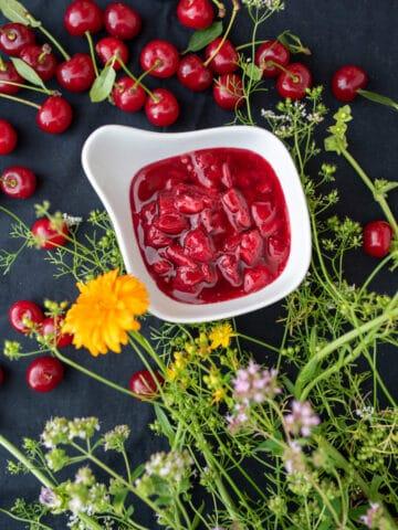 dżem z wiśni w białej miseczce na czarnym obrusie udekorowanym polnymi kwiatami i wiśniami