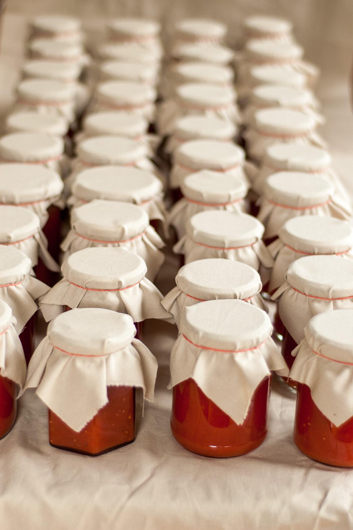 cztery rzędy słoików z przecierem pomidorowym po dziesięć w każdym rzędzie