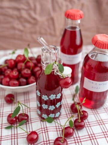 sok z wiśni w butelkach obok wiśnie