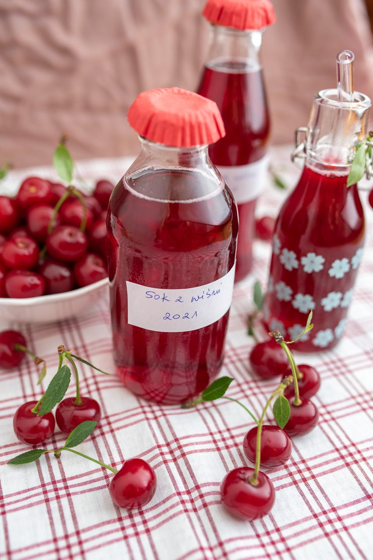 domowy sok z wiśni w butelkach ustawione na białym obrusie w czerwoną kratę
